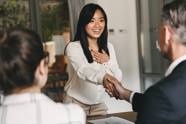 Happy woman shaking hands with a man in a business suit.